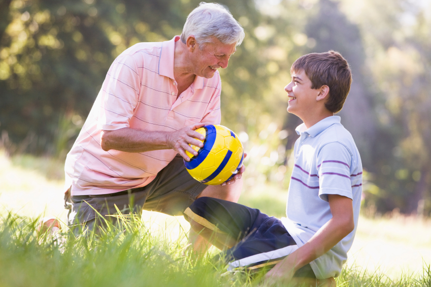 Grandfather and grandson at a park with a ball smiling