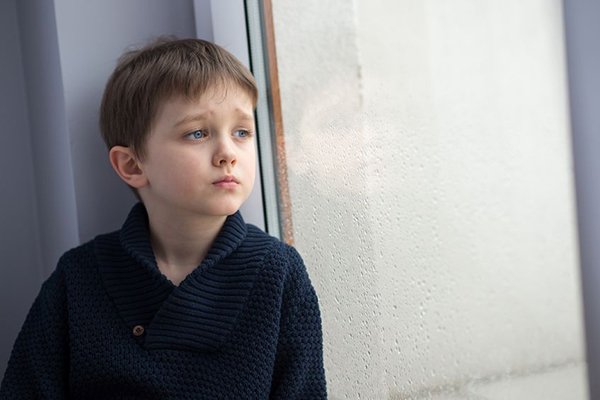 52086622 - sad 7 years boy child looking out the window. rainy day