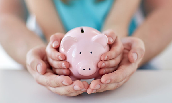 38662892 - family, children, money, investments and people concept - close up of father and daughter hands holding pink piggy bank
