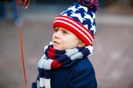 59895366 - little cute kid boy crying on christmas market in germany, outdoors. sad child.