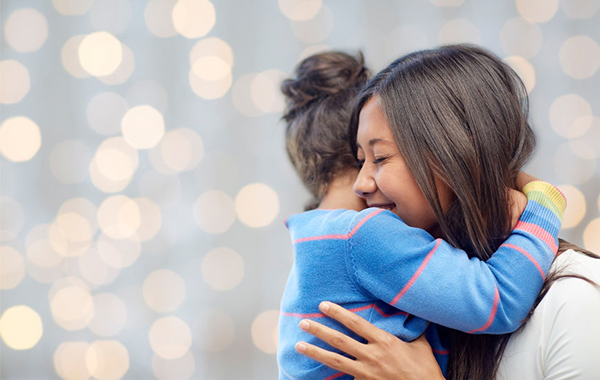 48506875 - family, children, love and happy people concept - happy mother and daughter hugging over lights background