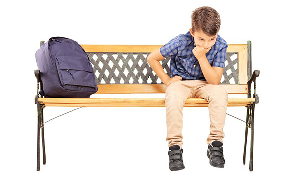 21285078 - school boy sitting on a bench and thinking, isolated on white background