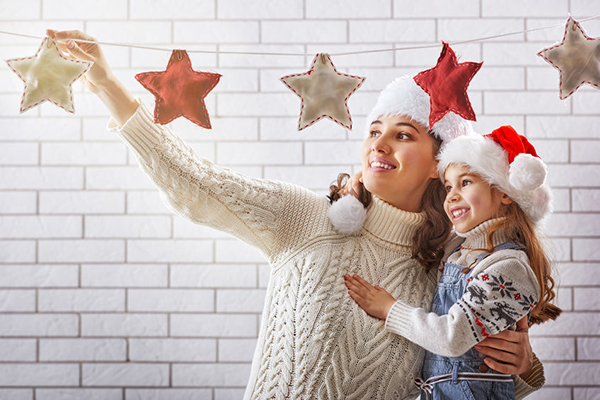 48423278 - merry christmas! happy mother and daughter hang a christmas garland.