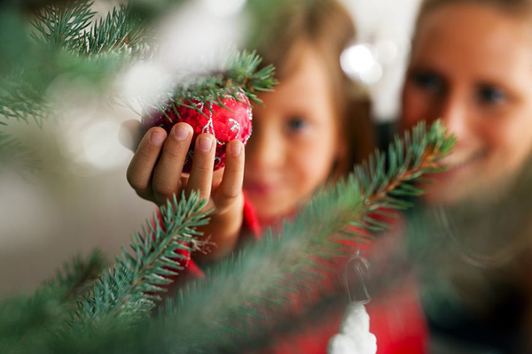 8037045 - young girl helping her mother decorating the christmas tree, holding some christmas baubles in her hand (focus on bauble)